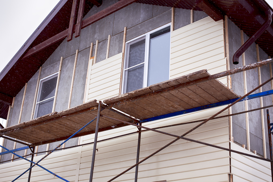 Scaffolding around house with beige siding covering walls. Construction site.